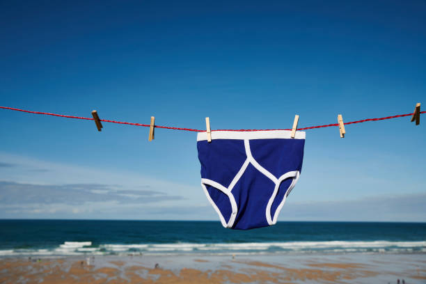 vintage bright blue y-front underpants on a washing line on cliffs overlooking a beach on a sunny day. - washing line stock pictures, royalty-free photos & images