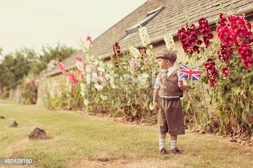 A young British boy in vintage clothing is celebrating his English heritage by waving the national flag of the United Kingdom. He is standing in front of holly hocks. Vintage toned.