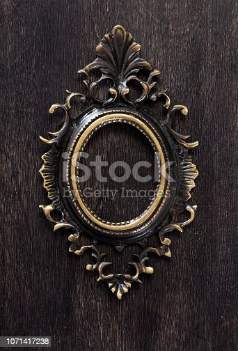 istock Vintage bronze frame on a wooden background, top view 1071417238