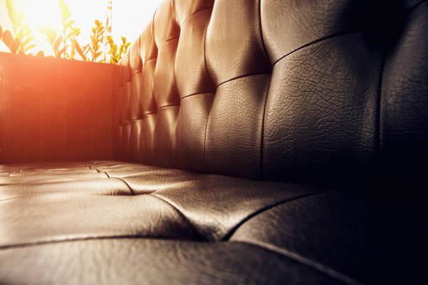 vintage braune ledercouch im abendlicht - ledersessel braun stock-fotos und bilder