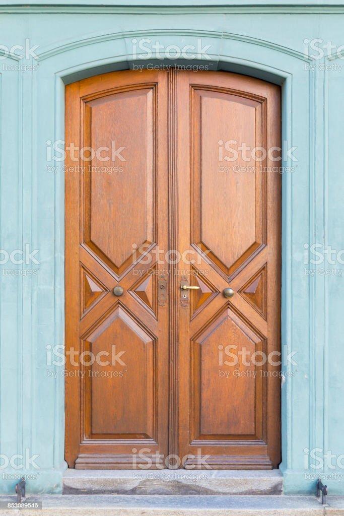 Vintage brown wooden door with green frame stock photo