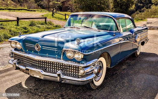 Classic Buick 1958 automobile, blue, with natural background.
