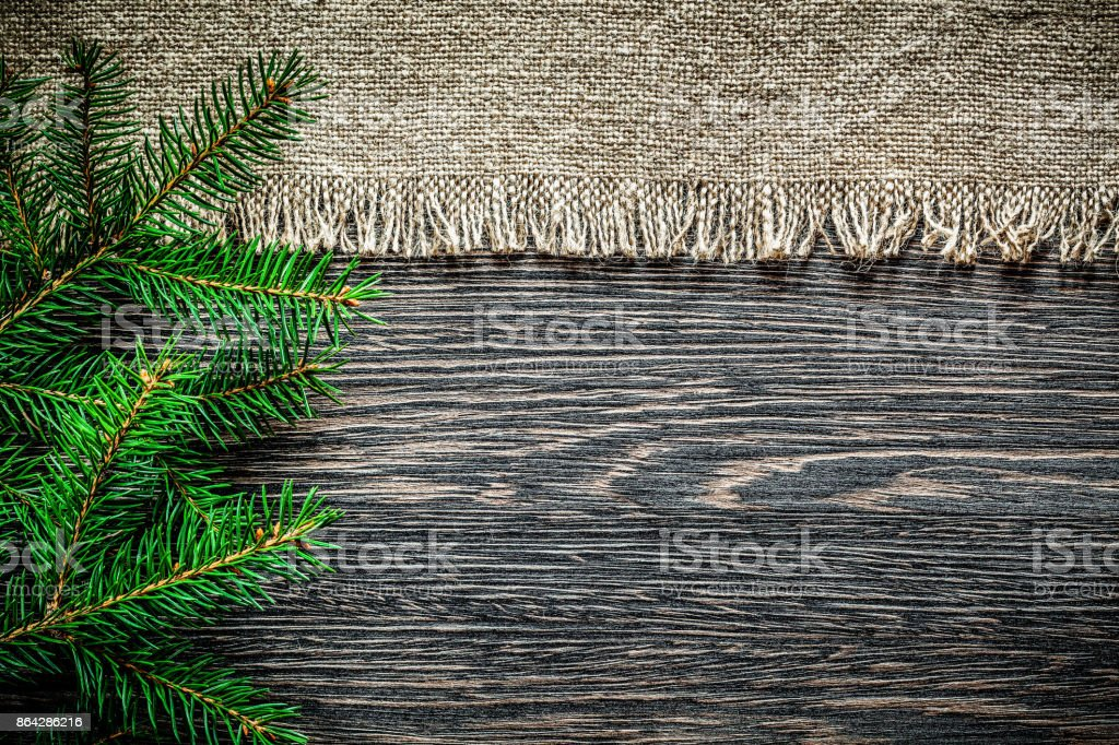 Vintage burlap pine branch on wooden board Christmas background royalty-free stock photo