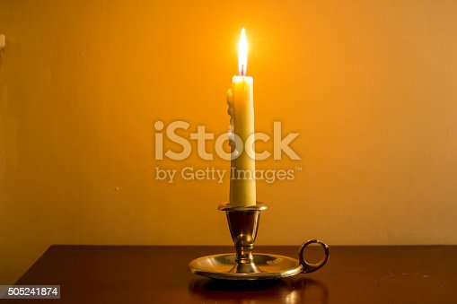 Vintage candle burning in antique candle holder on wooden table with plain background.