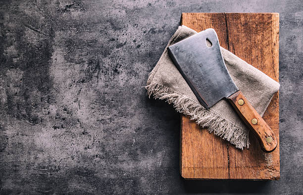 Vintage butcher meat cleavers on concrete or wooden board. - Photo