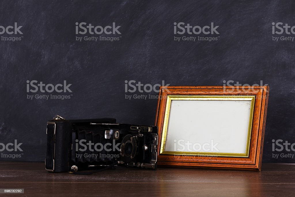 Vintage camera and frame against blackboard background foto royalty-free