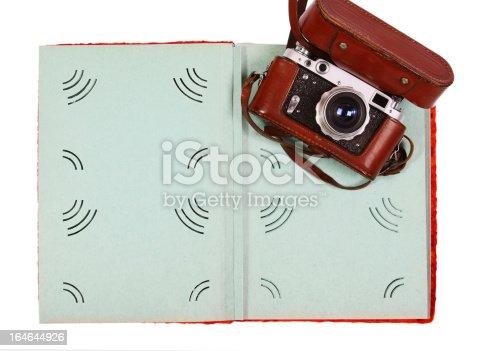609706398 istock photo Vintage camera and green photo album isolated on white background 164644926