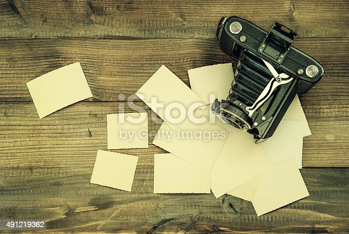 609706398 istock photo vintage camera and old photos on wooden background 491219362