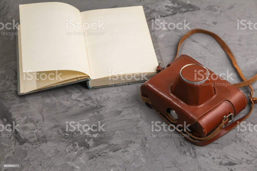Vintage camera in the case and old open book