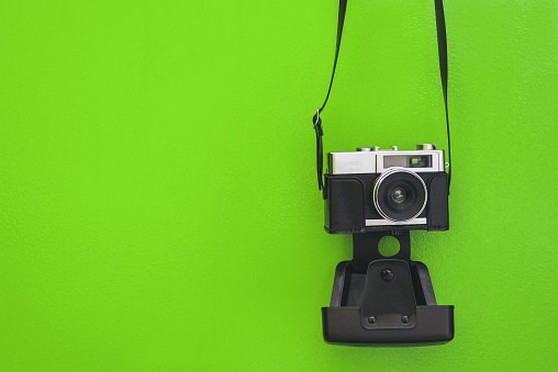 Vintage camera isolated at green wall