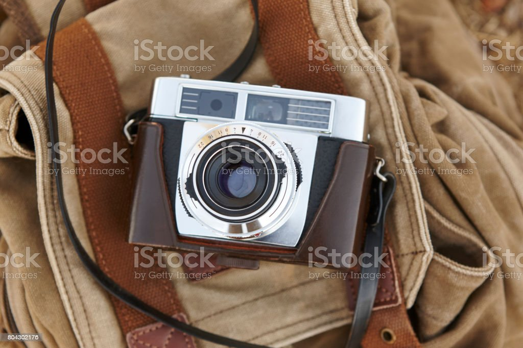 Vintage camera with backpack on the ground. Travel stock photo