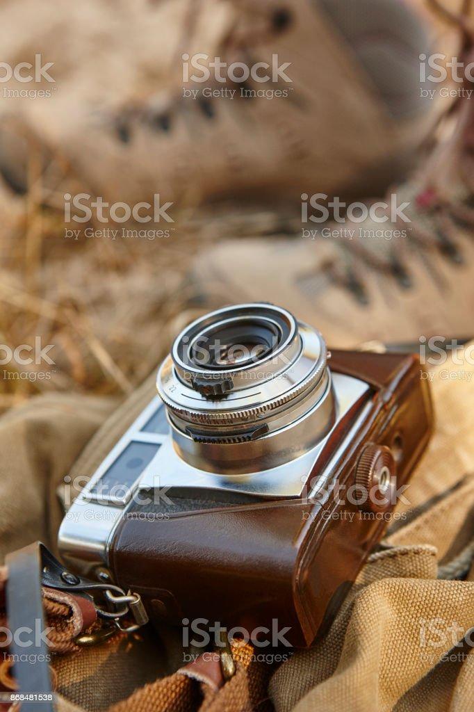 Vintage-Kamera mit Wanderschuhen auf dem Boden. Reisen – Foto