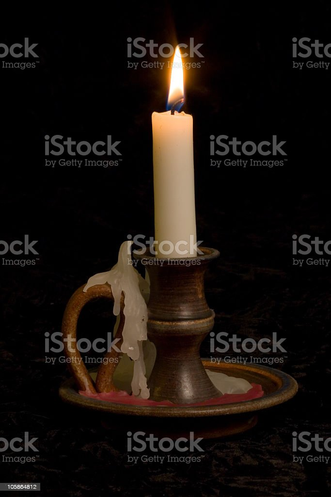 A vintage candle glowing in the dark stock photo