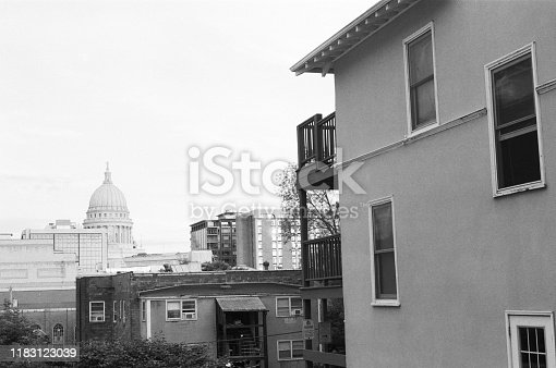 State capitol building of Madison, WI shot through apartment buildings in vintage black and white film stock for classic feel.