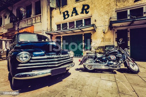 An old chevrolet and a motorbike in front of a bar in Jakarta