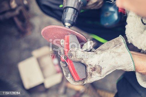 DIY - man repairing disc brake at vintage car, replacing brake pads at parking lot, sanding brake pads using multi tool with sand extender, real people