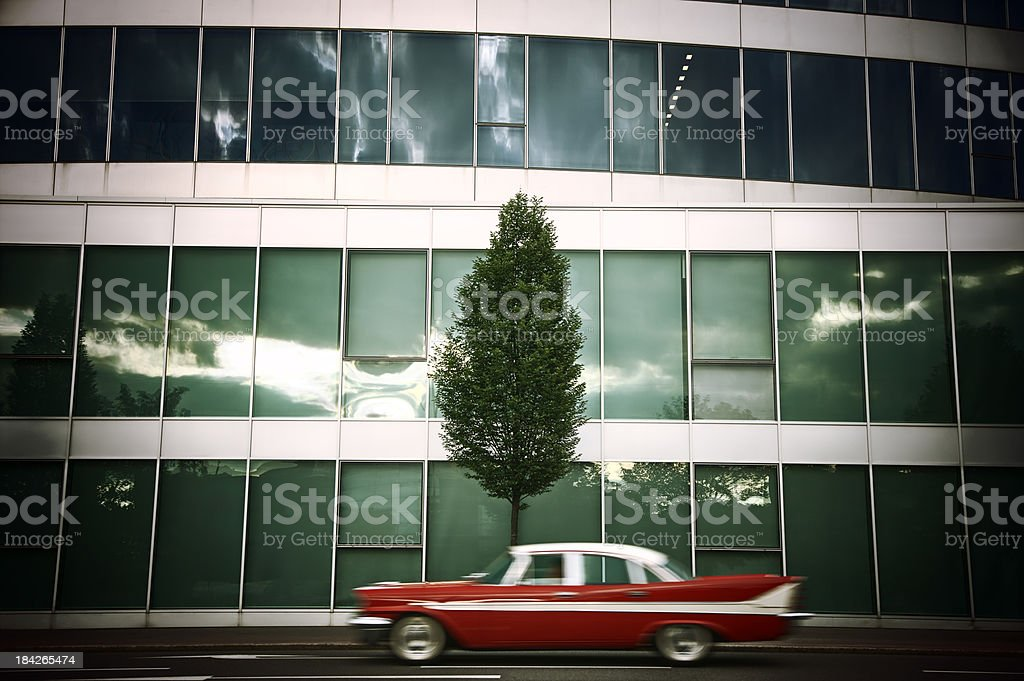 blurred classic car driving in front of a modern building,