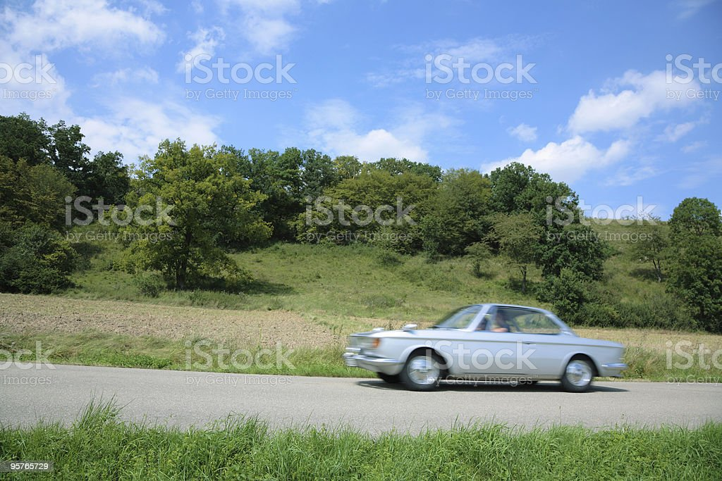 Vintage Car Driving Through Summer Landscape royalty-free stock photo