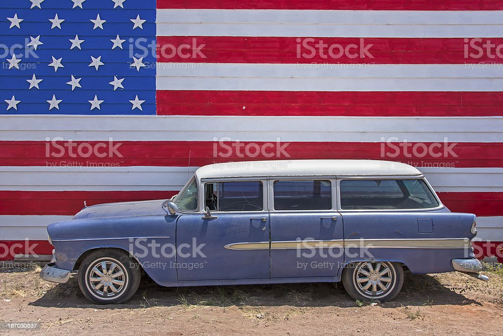 Vintage car in front of American flag royalty-free stock photo