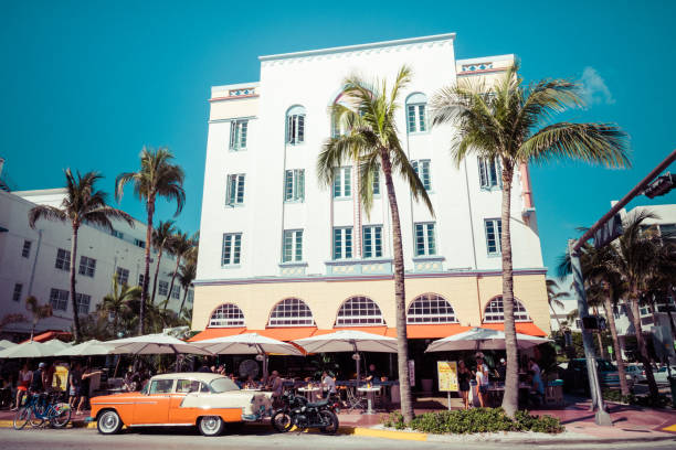 miami beach, florida, usa - february 18, 2018: vintage car parked along ocean drive in the famous art deco district in south beach. south beach, fl - art deco stock photos and pictures