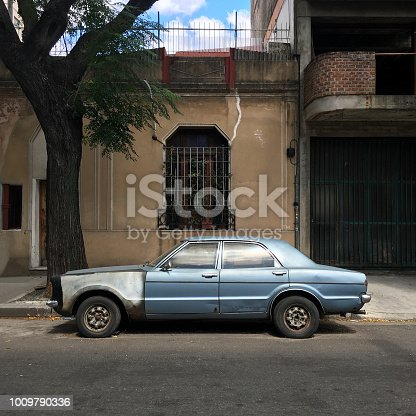 Old and deteriorated car parked in the street in Buenos Aires, Argentina