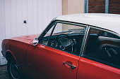 Red colored vintage car in front of a garage with a white roof