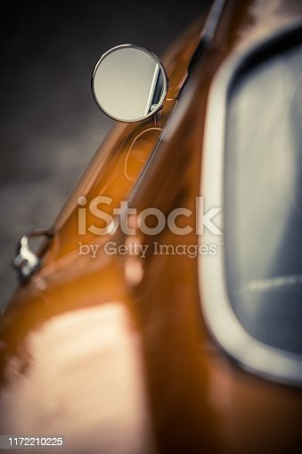 Close up shot of a vintage car side mirror.