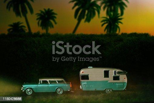 Vintage Automobile with Camper Driving on Highway at Dusk