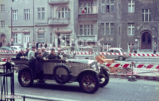 Berlin (West), Germany, 1967. Oldtimers with driver and guests on the way to a tunnel inauguration on Bundesplatz in West Berlin. Also: passers-by, shops, construction site and tenement houses.
