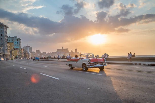 vintage cars driving along malecon, havana as sun goes down - cuba stock photos and pictures