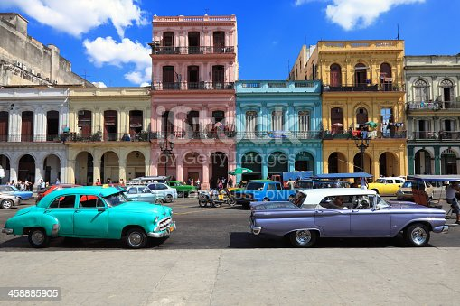 Havana, Сuba - February 12, 2013: Vintage cars moving on the streets of colorful Havana. A great variety of old cars exist In Cuba. On the streets cars from the first half of the 20th century can be found in magnificent conditions, which takes back in history and feel the old atmosphere of the cities.