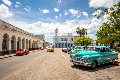 August 6, 2018 - Cienfuegos, Cuba: Vintage cars parked  in Jose Marti square with Palacio Ferrer, House Of The Culture, in the background