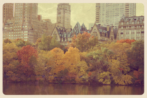 Retro-styled postcard of the colorful autumn trees along Central Park West in New York City. In the background is The Dakota -- a co-op apartment building located on the northwest corner of 72nd Street and Central Park West in the Upper West Side of Manhattan -- the location of the murder of John Lennon.