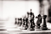 Chess pieces pawn and castle (rook) visible. Selective focus. Vintage outlook given. Some noise present.More Chess