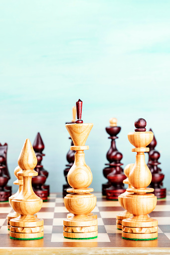 Vintage chess figures on a board at the very beginning of the game, on a teal background with copy space