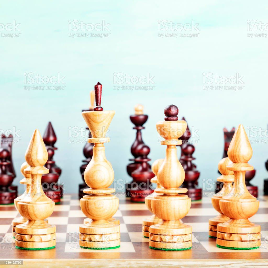 Vintage chess figures on a board at the very beginning of the game,...