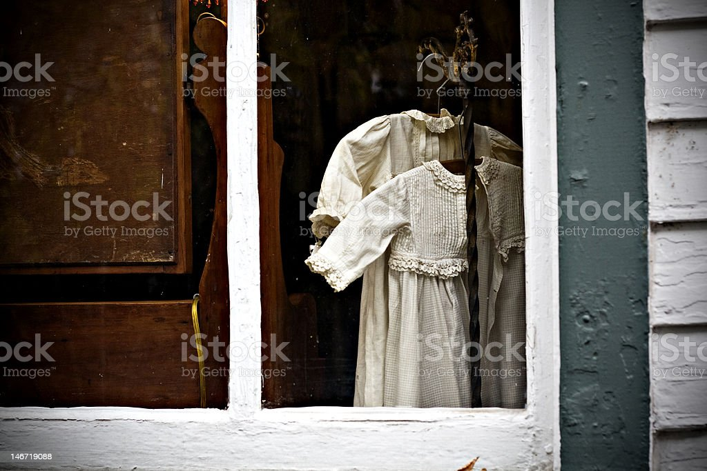 Vintage child's dress in antique window. stock photo