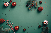 istock Vintage Christmas background with red and white balls decoration, fir tree branches, candy canes, confetti. Retro Christmas card template. 1287169114