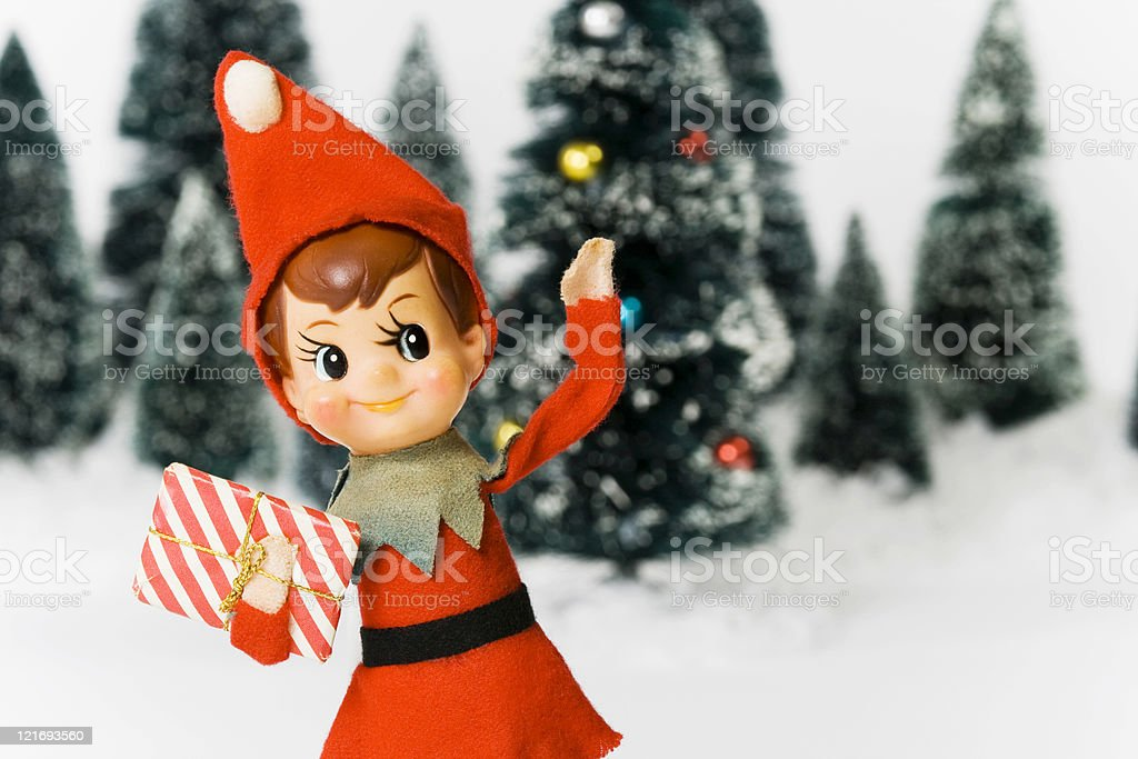 Vintage Christmas elf toy arranged with fur trees and snow stock photo