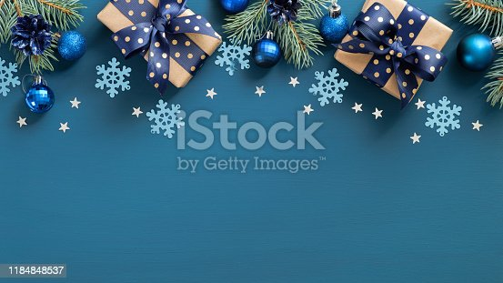 Vintage Christmas frame border. Flat lay fir three branches, blue balls and snowflakes over blue background. Top view, copy space. New Year greeting card template, Xmas postcard mockup.