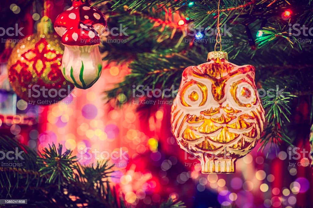 Vintage Christmas toy Owl hanging on a fir branch among the garlands...