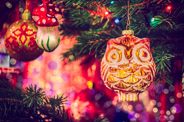 Vintage Christmas toy Owl hanging on a fir branch among the garlands on a blurred bokeh background stock photo