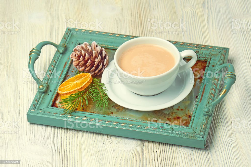 Vintage Christmas tray with a Cup of cappuccino decorated with a slice of orange, cedar cones, fir tree branches stock photo