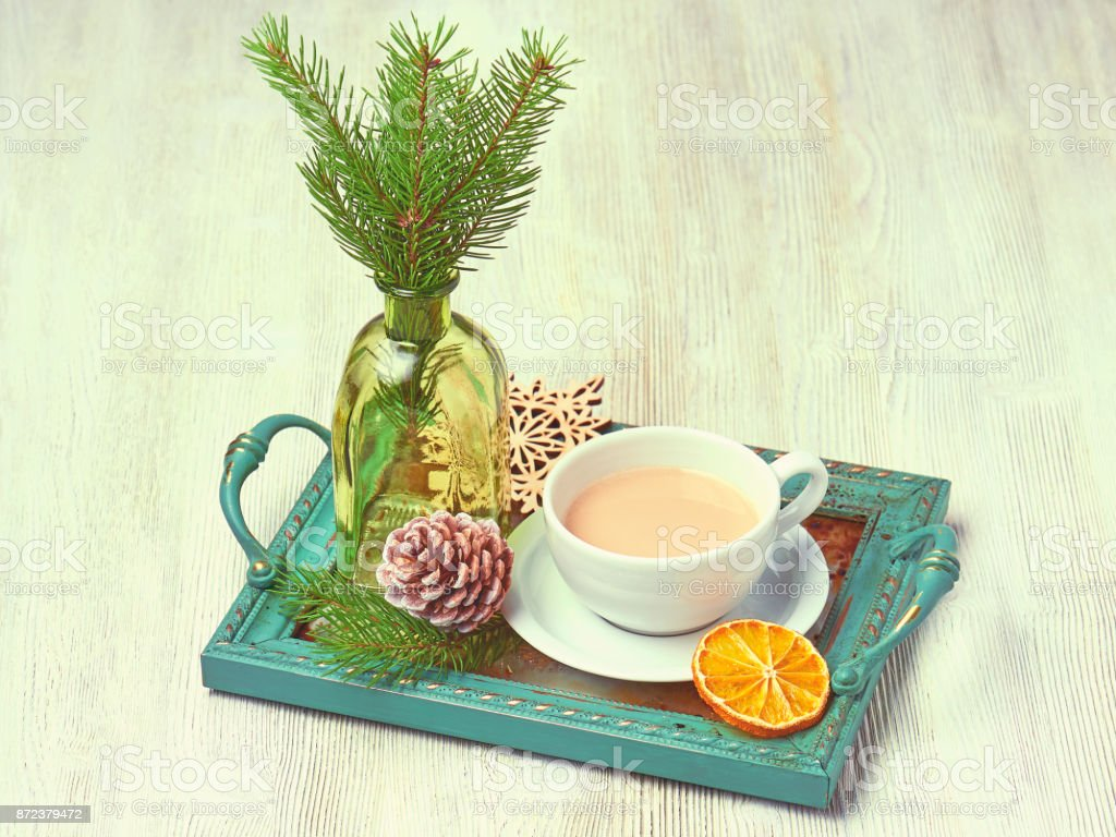 Vintage Christmas tray with a Cup of cappuccino decorated with a slice of orange, cedar cones, fir tree branches and glass bottle stock photo