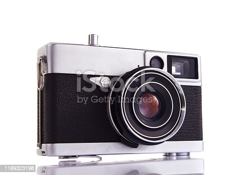 Vintage chrome and black rangefinder film camera on white background with a flare in the lens