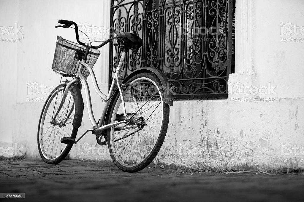 Vintage Chromed com cesto de bicicleta ao lado de uma janela da casa foto royalty-free