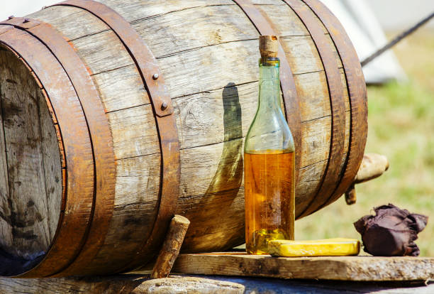 vintage cider barrrel with bottle on table Closeup of vintage wooden barrrel and cider bottle on table at outdoor calvados stock pictures, royalty-free photos & images