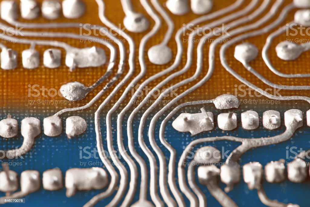 Vintage circuit board with soldering trace. Backside brown blue electronic chip retro style design. Macro view, shallow depth of field stock photo