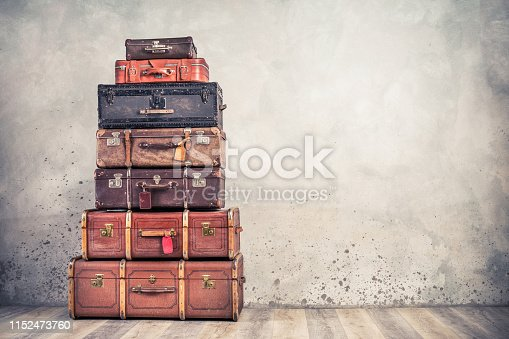 istock Vintage classic outdated trunks luggage with tags, old antique leather suitcases tower front concrete wall background. Travel baggage concept. Retro style filtered photo 1152473760