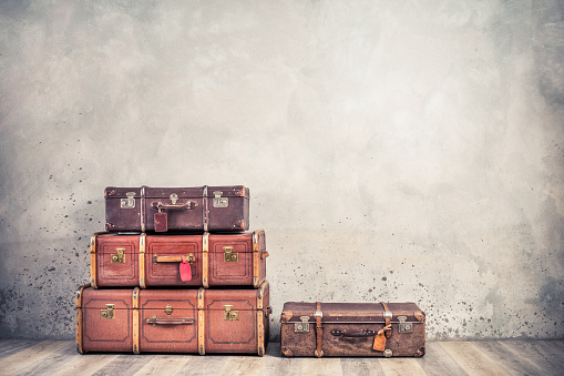 Vintage classic outdated trunks luggage with tags, old antique leather suitcases front textured aged concrete wall background. Travel baggage concept. Retro style filtered photo